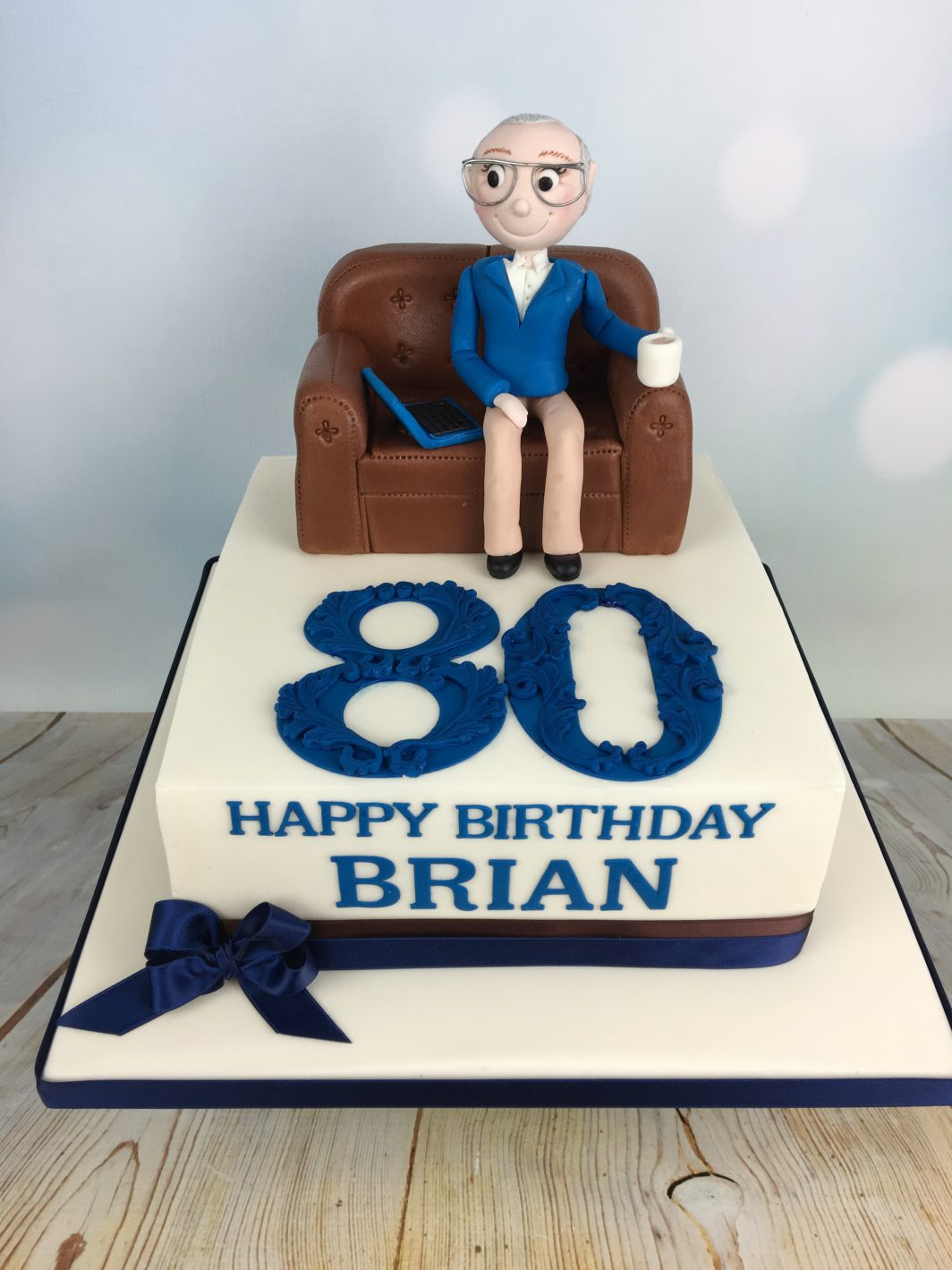 80th Birthday Cake With Figure Sat On Sofa