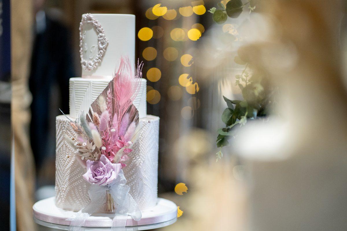 Pretty blush wedding cake with a pampas grass spray